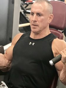 Greg Rando m3 mind muscle memory seated biceps curl exercise in flex position to end The Hyper 6 Muscle Strength System